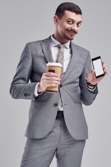 Portrait of handsome young confident arabic businessman with fancy mustache in fashion gray full suit holds a cup of coffee and phone on