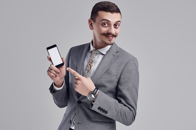 Portrait of handsome young confident arabic businessman with fancy mustache in fashion gray full suit points to the phone on