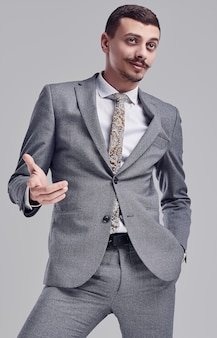 Portrait of handsome young confident arabic businessman with fancy mustache in fashion gray full suit