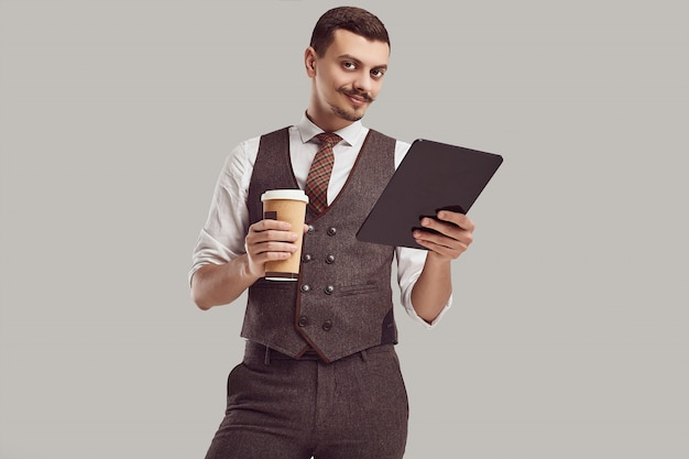 Portrait of handsome young confident arabic businessman with fancy mustache holds tablet and cup of coffee