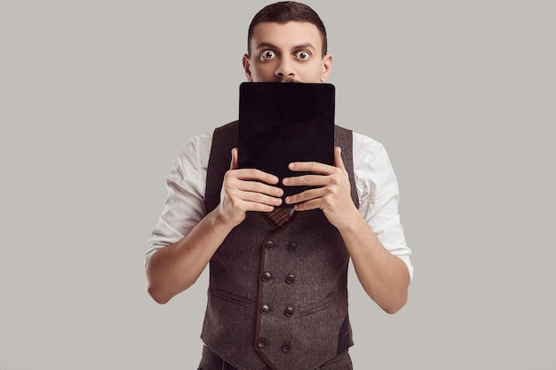 Portrait of handsome young confident arabic businessman with fancy mustache holds tablet