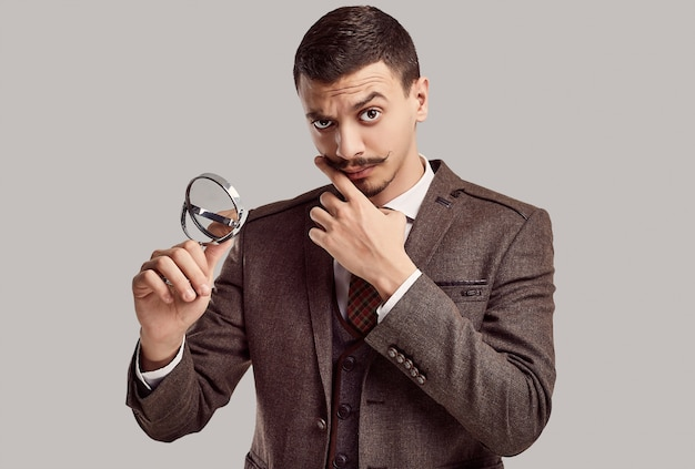 Portrait of handsome young confident arabic businessman with fancy mustache in woolen brown full suit looking in a small mirror