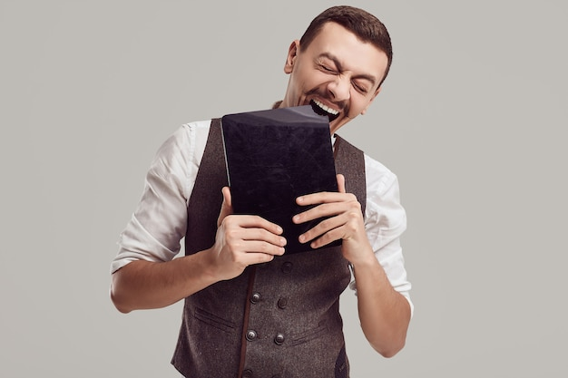 Portrait of handsome young confident arabic businessman with fancy mustache in woolen brown suit holds tablet on studio background