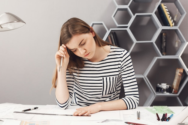 Portrait of handsome young dark-haired european freelance girl in striped shirt drawing, looking with serious and concentrated face expression at papers, looking through her work.