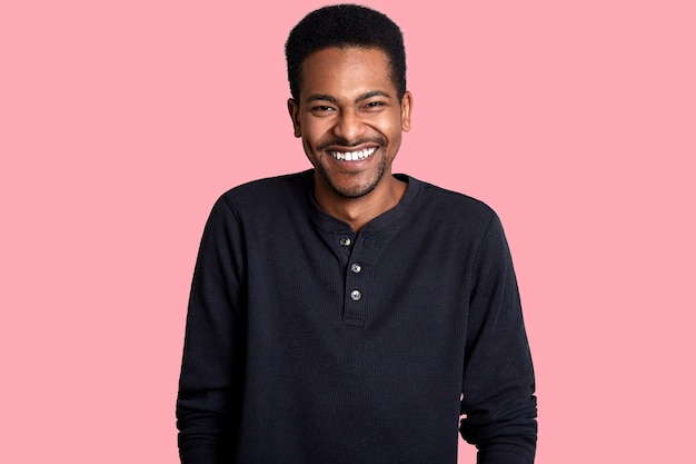 Portrait of handsome young dark skinned man. good looking laughing male poses in studio, guy hears funny joke. cheerful boy stands isolated on pink. people and comunication concept.