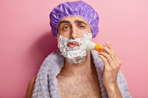 Portrait of handsome young european man applies shaving foam on face with brush, prepares for shave, wears showercap, has soft towel around neck, stands topless indoor. masculine skin care concept