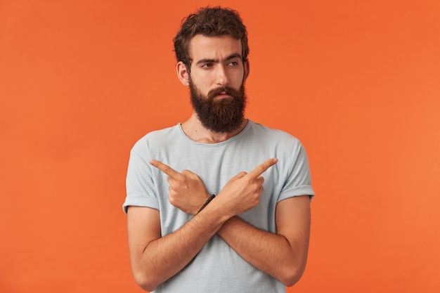 Portrait of handsome young guy with brown eyes wearing white t-shirt casual clothes is pointing fingers asides emotion attentive and confident looking aside standing against red wall