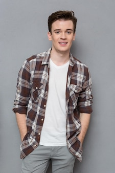 Portrait of handsome young happy positive man in checkered shirt  posing and smiling on gray wall