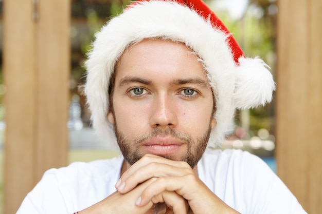Ritratto di uomo giovane e bello hipster con stoppie e sorriso fiducioso in posa all'interno, tenendo le mani giunte, indossando il cappello di babbo natale rosso con pelliccia bianca