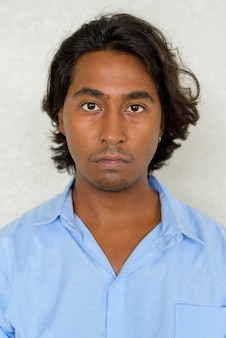 Portrait of handsome young indian man against plain background outdoors shot with natural light