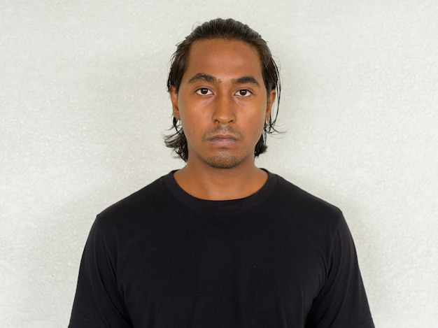 Portrait of handsome young indian man against plain background
