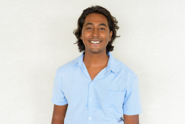 Portrait of handsome young indian man smiling against plain background