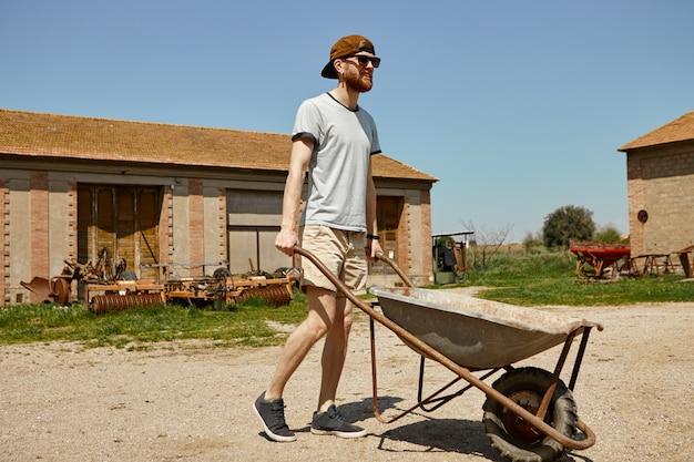 Ritratto di hipster maschio giovane bello in snapback e occhiali da sole che trasportano carrello dal magazzino