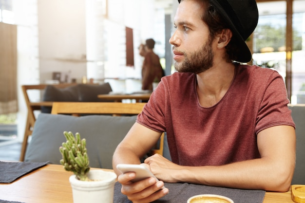 Portrait of handsome young male with stubble sitting at wooden table, holding generic smart phone