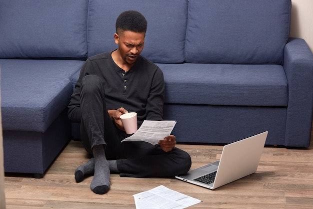 Portrait of handsome young man in black casual outfit, sitting on floor with laptop computer, working with papers and drinking coffee