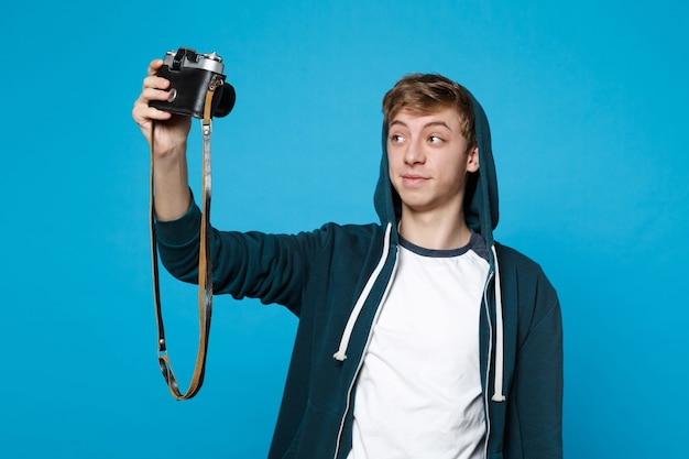 Portrait of handsome young man in casual clothes doing selfie shot on retro vintage photo camera isolated on blue wall . people sincere emotions, lifestyle concept.