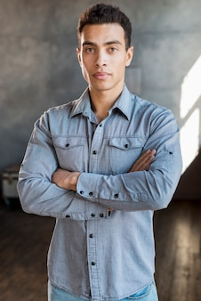 Portrait of a handsome young man in denim shirt with his arm crossed looking at camera