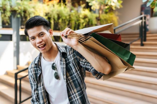彼は紙袋を持ってニヤリと笑う肖像画ハンサムな若い男
