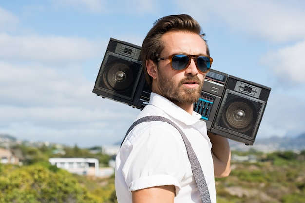 Portrait of a handsome young man holding radio near ears
