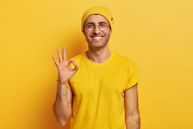 Il ritratto di un bel giovane fa il gesto giusto, dimostra accordo, ama l'idea, sorride felice, indossa occhiali da vista, cappello giallo e maglietta, modelli al coperto. va bene, grazie. segno della mano