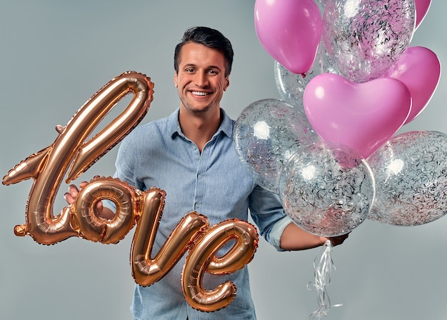 Portrait of handsome young man in shirt is standing on grey with air balloon labeled love in hands and heart shaped balloons.
