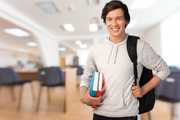 Portrait of handsome young man standing with books looking at camera