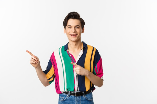 Portrait of handsome young man in stylish clothes, pointing fingers left and smiling, showing advertisement, standing over white