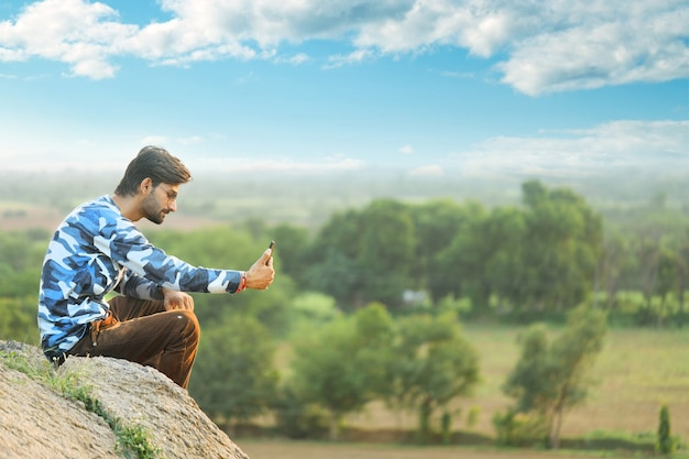 Portrait of a handsome young man taking selfie on mobile phone in outdoor