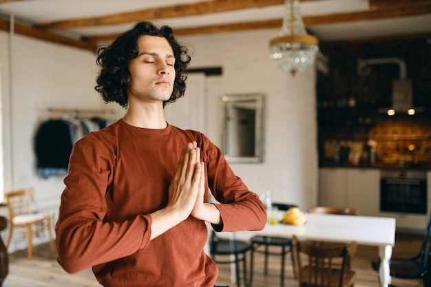 Portrait of handsome young man with black curly hair posing in cozy kitchen interior keeping eyes closed and pressing hands together in namaste, praying, doing meditation, having calm look