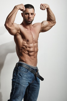 Portrait of a handsome young man with great physique over white wall Premium Photo