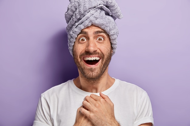 Portrait of handsome young man with happy expression, wears towel just after shower, surprised to have soft skin, dressed in casual white t shirt