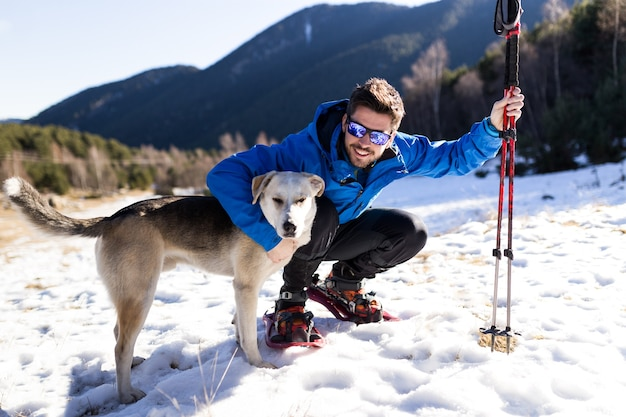 Portrait of handsome young man with his dog over winter background.