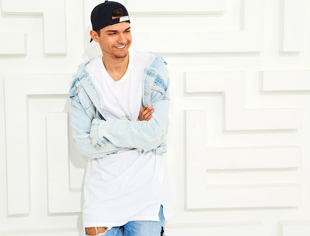 Portrait of handsome young model man dressed in jeans clothes posing near white textured wall