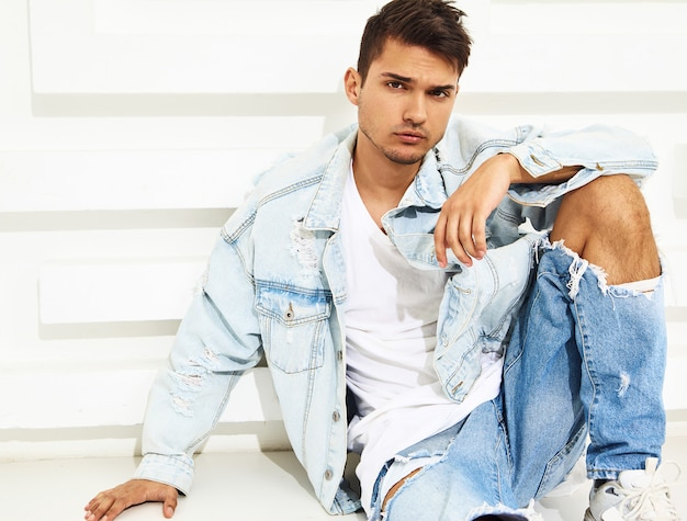Portrait of handsome young model man dressed in jeans clothes sitting near white textured wall
