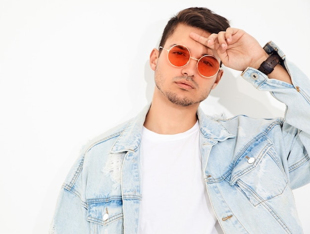 Portrait of handsome young model man dressed in jeans clothes in sunglasses posing. isolated