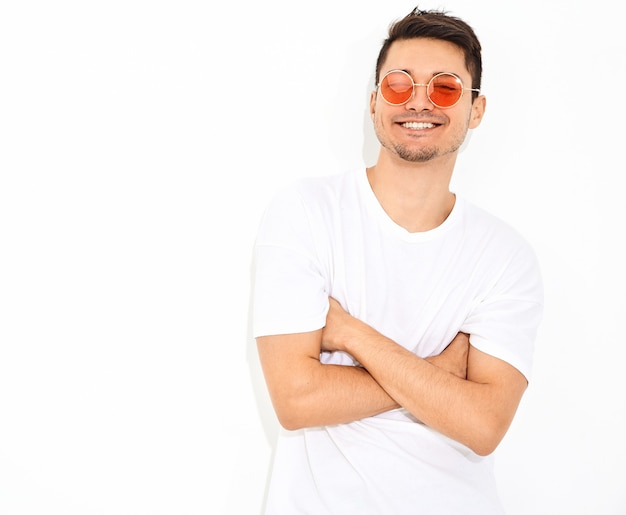 Portrait of handsome young model man dressed in jeans clothes  and t-shirt in sunglasses posing. crossed arms