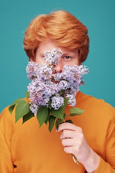 Portrait of handsome young redhead guy covering face behind lilac twigs, stop allergy concept