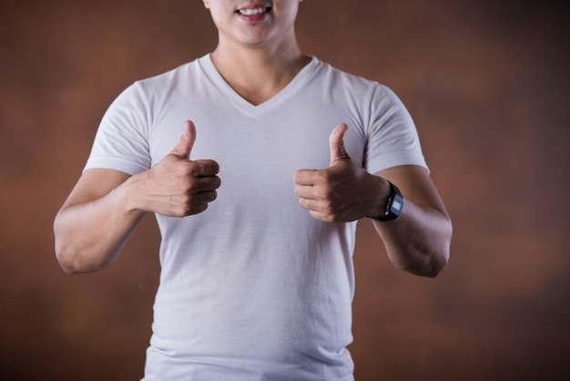 Portrait handsome young smiling man giving thumbs up pointing fingers