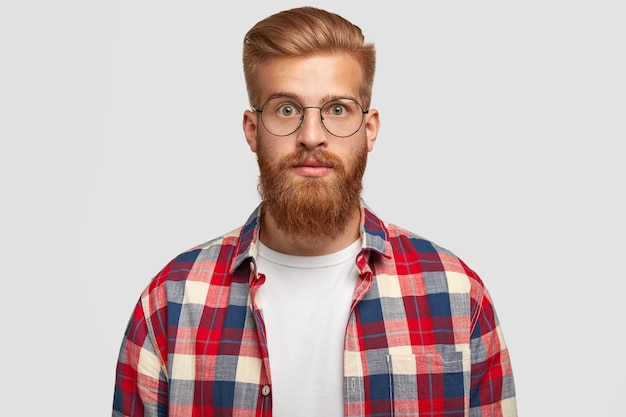 Portrait of handsome young successful man designer with thick ginger beard, looks surprisingly