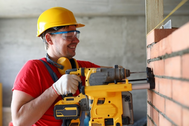 Portrait of handyman builder using perforator to drill hole in constructed wall. repairing or fixing, industry worker with instrument for job completion