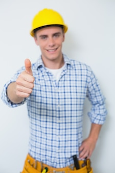 Portrait of a handyman in yellow hard hat gesturing thumbs up
