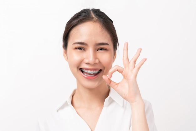 Portrait happily asian woman shows ok sign and braces smiling on white wall,