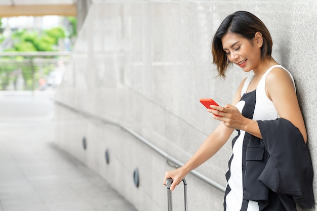 Portrait happily young beautiful woman standing near wall smiling and use smartphone