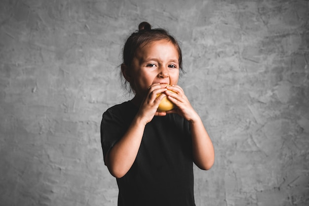 Portrait of a happiness little girl eating a green apple on gray background.