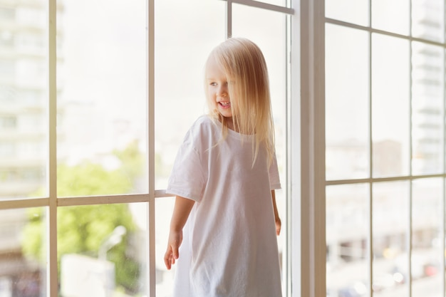 Portrait of happy 3-year-old pretty girl wearing blank white dress smiling while looking at window