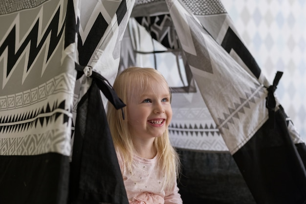 Portrait of happy 3-year-old toddler girl girl smiling while sitting in children play tent or play house.