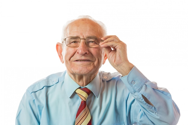 Portrait of happy 90 year old senior man holding glasses, smiling and looking at camera isolated on white background.