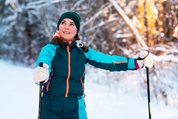 Portrait of happy active beautiful young woman skiing