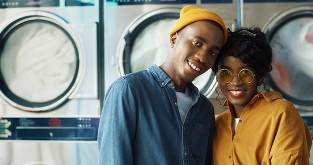 Portrait of happy african american cheerful couple in love hugging and smiling to camera in laundry service. joyful young man and woman standing at working washing machines inside washhouse.