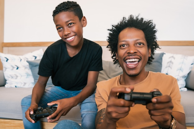 Portrait of happy african american father and son sitting in sofa couch and playing console video games together at home. family and technology concept.